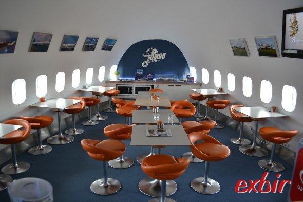 """Aufenthaltsraum&Bistro in der Nase im Lower Deck.  Hier wird auch das Frühstück serviert. Eigene  Gerichte können in den """"Gäste-Microwellen""""aufgewärmt werden.   Die Wand zieren Fotos des bewegten Lebens der Boeing 747212B.  Foto: Christian Maskos"""