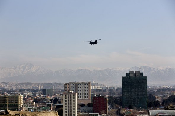 A military helicopter over the roofs from Kabul. photo: Josh Cahill