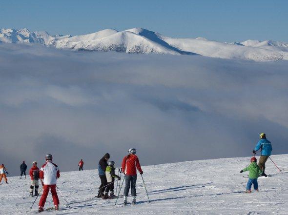 Über den Wolken - Touristen im Skigebiet Gerlitzen. Der Zugang zu den Skigebieten der Alpen ist besonders unkompliziert, wenn man seine Skireise direkt inkl. Skipass bucht. Urheber: Horst Gutmann, creative commons